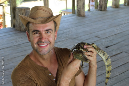 Human interacting with a baby caiman