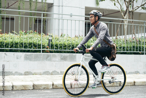 Photo Young Asian man wearing casual clothes, glasses and safety helmet riding bicycle