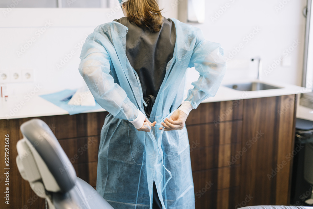 Fototapeta Assistant dresses a surgical gown surgeon in the operating room