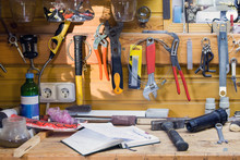 Wooden Workbench At Workshop. Lot Of Different Tools For Diy And Repair Works. Wood Messy Table With Notebook. Copyspace. Labour Day