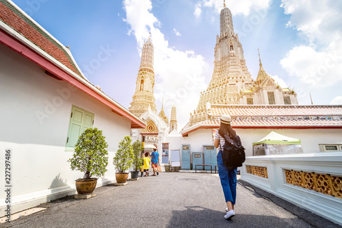 Photo  Tourist women with Carrying a backpack Viewing poster, About the temple in Bangkok At Arunratchawararam Temple