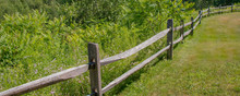 Curved Wooden Fence Between Grass And Meadow