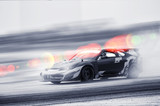 Car drifting, Blurred of image diffusion race drift car with lots of smoke from burning tires on speed track - 227305449
