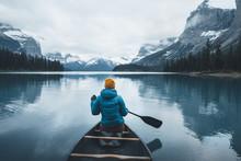 Girl Paddling On A Blue Lake