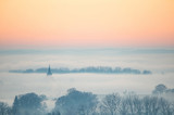 church spire juting out from the fog at sunset in autumn - Austria - 227306077