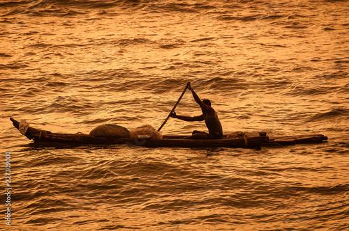 Fotografie, Obraz  Lone fisherman rowing - India