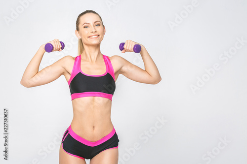 Foto op Plexiglas Fitness Portrait of happy young fitness woman with dumbbells and perfect body smiling and energetic. Isolated over white background.