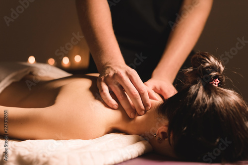 Stampa su Tela  Men's hands make a therapeutic neck massage for a girl lying on a massage couch in a massage spa with dark lighting