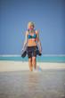 Snorkel woman walking through shallow water on Maldives