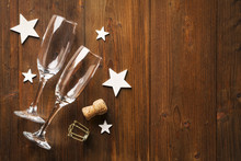 New Year's Eve Champagne Glass And Wihte Stars On Old Wooden Floor