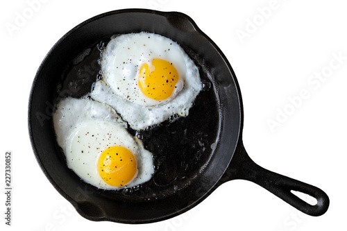 Poster Ouf Two fried eggs in cast iron frying pan sprinkled with ground black pepper. Isolated on white from above.