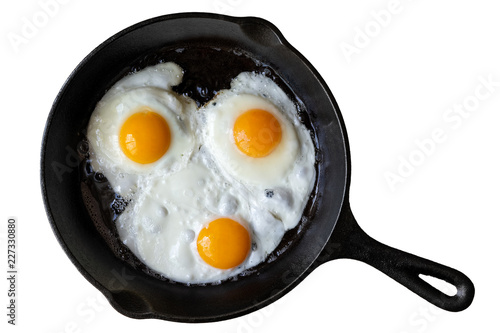 Poster Ouf Three fried eggs in cast iron frying pan isolated on white from above.