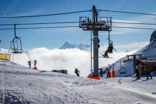 People skiing and sitting in a chairlift in Espace Killy the ski resorts of Tignes and Val D'Isere. Espace Killy is a name given to a ski area in the Tarentaise Valley, Savoie in the French Alp