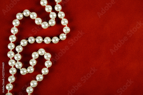 Leinwand Poster White pearl necklace on red leather background.