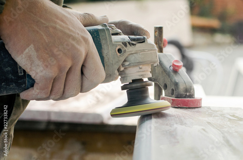 Obraz A man polishing a gray marble stone with a small angle grinder. working man the creation of monuments - fototapety do salonu