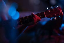 Woman's Hand Plays Guitar Chord In Stage Lighting