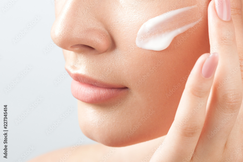 Fototapeta Young beautiful woman applies cream on clean perfect skin