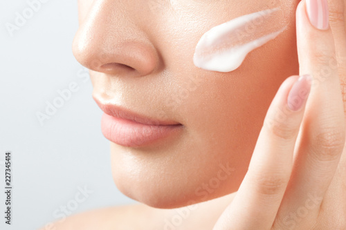 Young beautiful woman applies cream on clean perfect skin Canvas