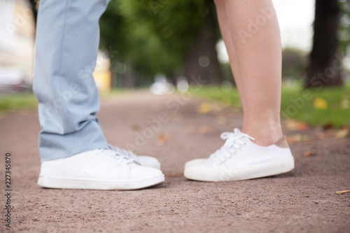 Close up girl and guy legs feet in white gumshoes standing outdoors in park Canvas Print