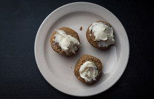 Three Frosted Muffins On A Plate