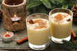 Eggnog in glasses with cinamon on wooden table