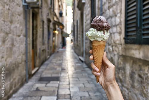 Keuken foto achterwand Historisch geb. Female hand with ice cream in waffle cone on old street backgrou
