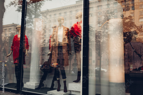 Manikins dressed in autumn outfits on showcase of a store in city center. Shopping and sales concept