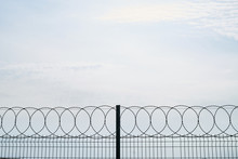 Barbed Wire Against Cloudy Sky...