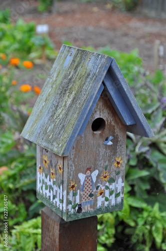 Fotografering Old wooden birdhouse in garden