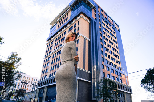 Fotografie, Obraz  A girl with a beautiful figure in a gray dress near a tall building