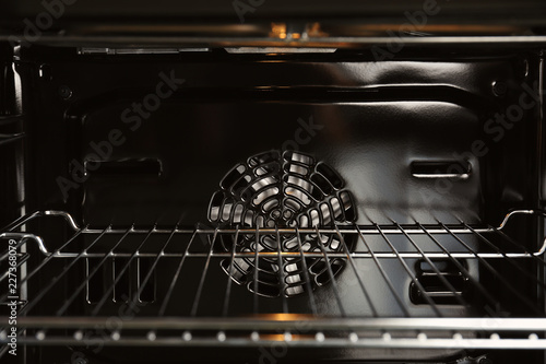 Open empty electric oven with rack, closeup. Inside view
