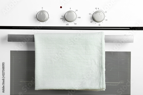 Modern electric oven with towel, closeup view