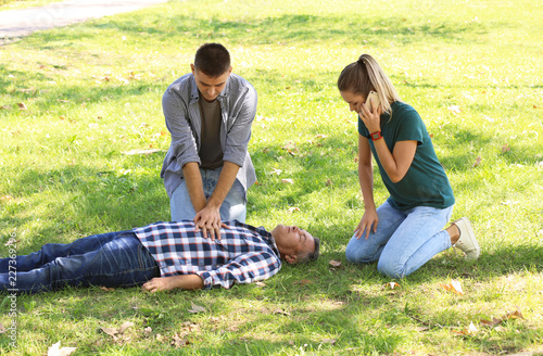 Fotografía  Passersby helping unconscious man outdoors. First aid