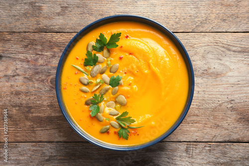 Delicious pumpkin cream soup in bowl on wooden background, top view