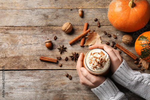 Foto Woman holding glass of tasty pumpkin spice latte on wooden table, flat lay with