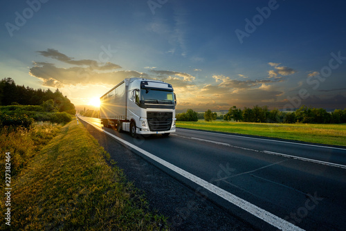 Fotografiet  White truck driving on the asphalt road in rural landscape in the rays of the su