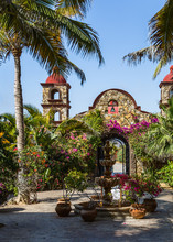 Mexican Mission Church With Palm Trees And Flowers
