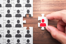 Human Resource Management. Selecting Person For The Job. Personnel, Employment And Recruitment Concept. Assembling Jigsaw Puzzle Pieces On Wood Desk.