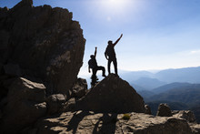Concept Of Two Successful People At The Top Of The Mountains