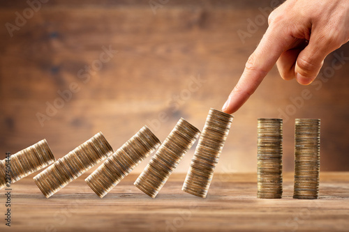 Businessperson Protecting Stacked Coins From Falling On Desk