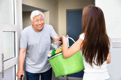 Fototapeta Man Offering Help To His Daughter Carrying Groceries obraz