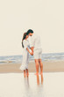 Happy couple going honeymoon travel on tropical sand beach in summer.