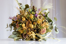 Close Up Of Wedding Bouquet Of Dried Flowers Lying On A White Table