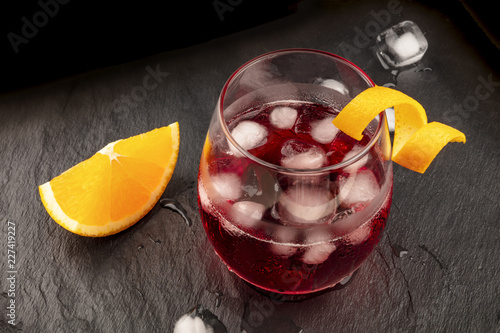 Fotobehang Cocktail A photo of a vibrant cocktail with campari and an orange curl garnish, with ice cubes on a black background, with copy space
