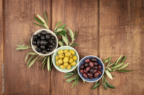 A top shot of various olives in bowls with a place for text