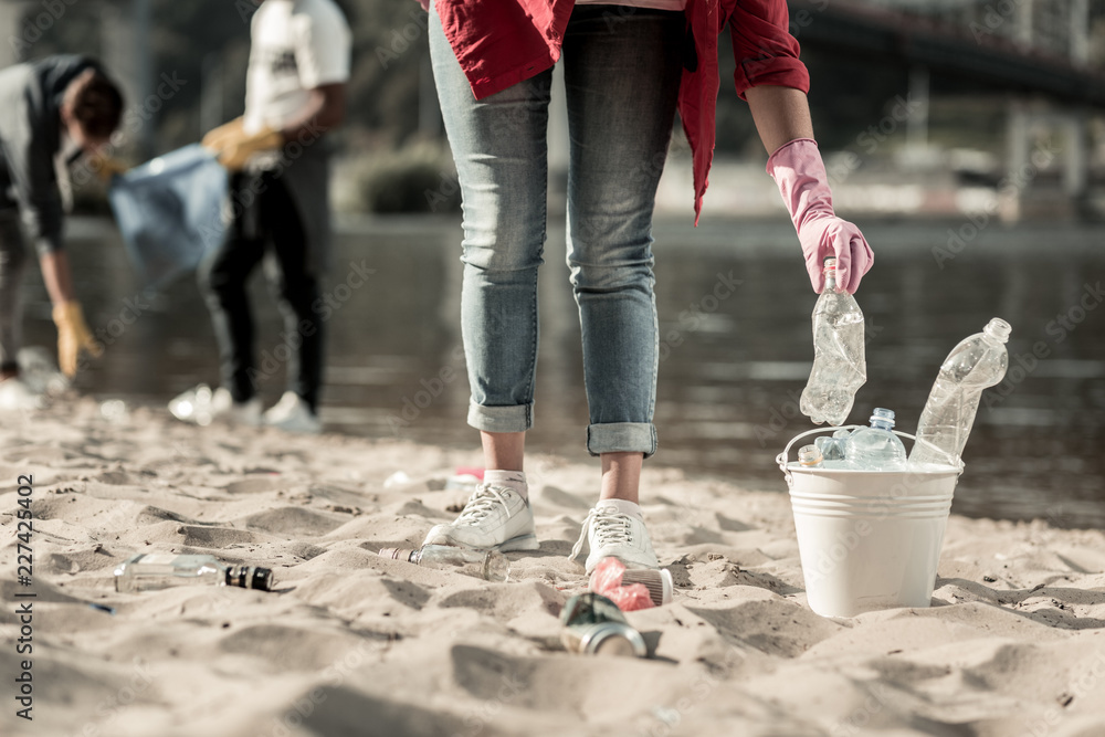 Fototapeta Trash on beach. Active responsible student wearing jeans volunteering while cleaning up trash left behind on the beach