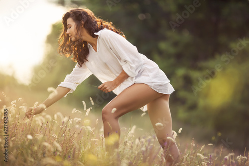 Photo  Beautiful young sexy woman in white dress collecting wild flowers at the rural sunny landscape background in summer