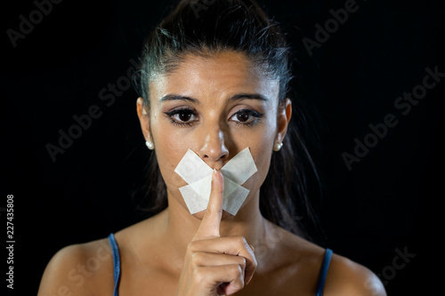 Valokuva  Attractive young woman mouth sealed on adhesive tape and silence gesture