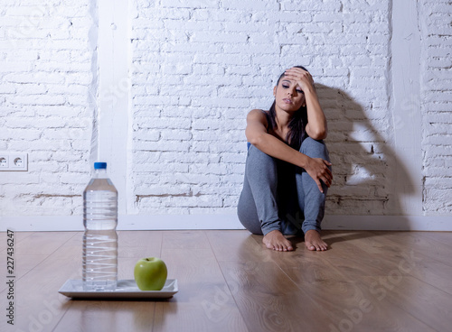 Depressed starving young woman on apple and water diet Canvas-taulu