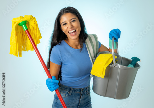 Young attractive woman holding cleaning tools and products in bucket isolated on blue background